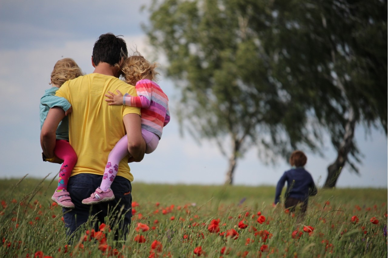 Self-Managed Superannuation: A family walking through a meadow. A man carries two young girls while a young boy runs ahead towards some trees.