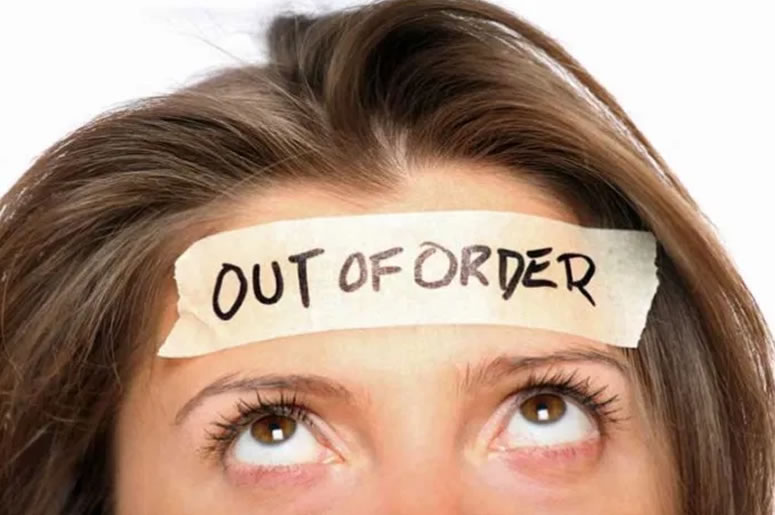 A close up of a lady's eyes and forehead. She's looking up at a sticker on her head with 'Out of Order' written on it.
