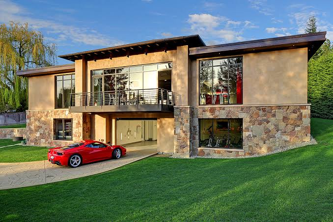 A large house with an expensive sports car on the drive.