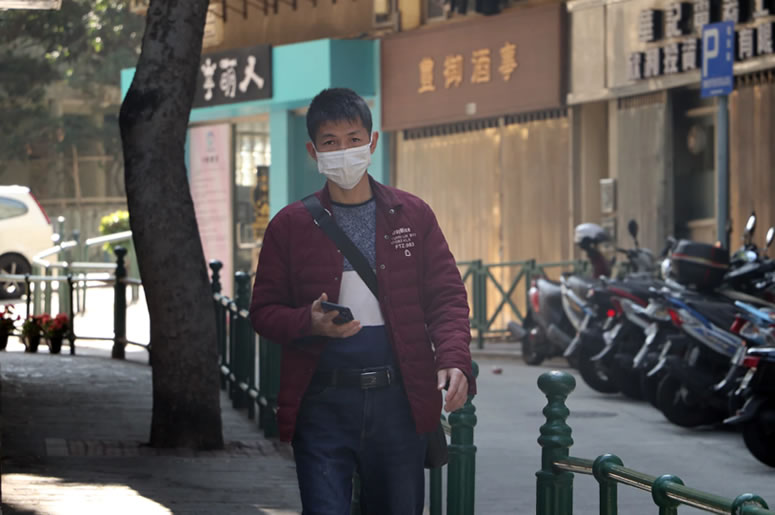 Coronavirus: Market Volatility - A Chinese man wears a face mask to help protect him from the Coronavirus while walking in the street.