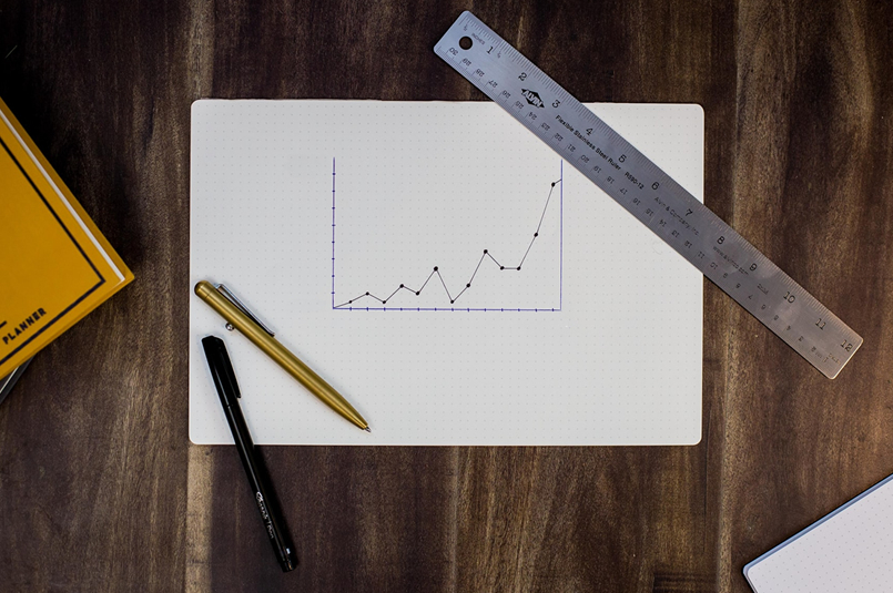 Balanced Investments, or Super Misleading?: A hand-drawn line graph on graph paper, surrounded by stationary on a desk top.
