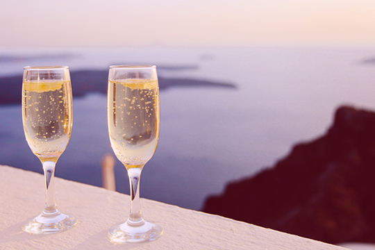 Two glasses of bubbling champagne on a ledge, in the evening sun, with sea views in the background. - Baldwin Financial Services | Prospect Financial Advisors.