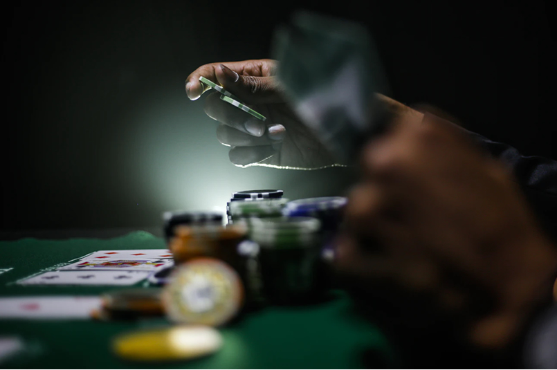 Investing Versus Gambling: The hands of a person playing poker in a dark room, with cards and poker chips on the table in front of him.