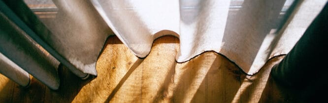 Looking down at semi-transparent curtains hanging slightly above a sun lit wooden floor.