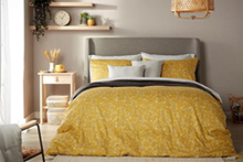 A double bed dressed in a yellow duvet cover, with matching and contrasting white pillowcases.