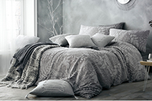 A cosy-looking double bed dressed in a grey patterned duvet cover, with a range of contrasting cushions and throws scattered upon it.